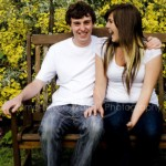 a laughing boy and girl on a bench during an on-location photoshoot