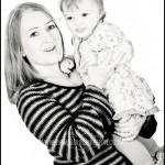 Mother holding smiling baby taken at portrait photography studio in Burnham