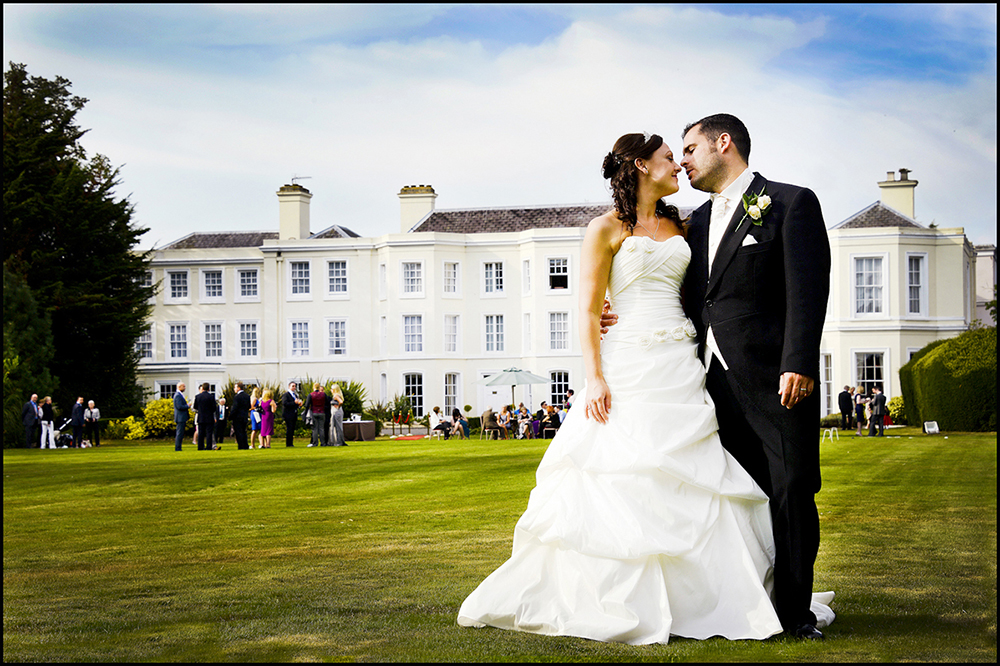 Wedding Couple kissing in front of a grand house for the photographer from Burnham, Slough