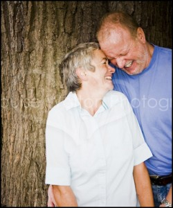 Couple laughing against a tree - Portrait & Family Photographer