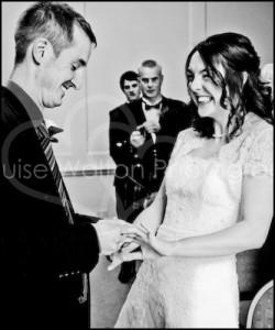 Smiling Groom placing ring on ecstatic bride - Wedding Photographer