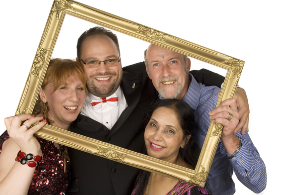 A photo from our Photobooth hire service in Burnham. Two ladies and two guys posing and smiling through a golden picture frame