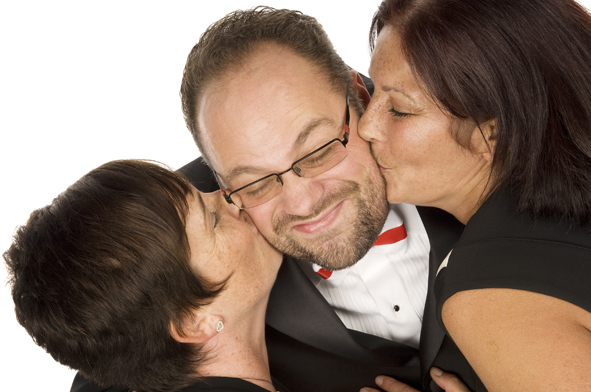 Photo of two ladies kissing either cheek of a smiling man wearing a tuxedo and a St. George bowtie