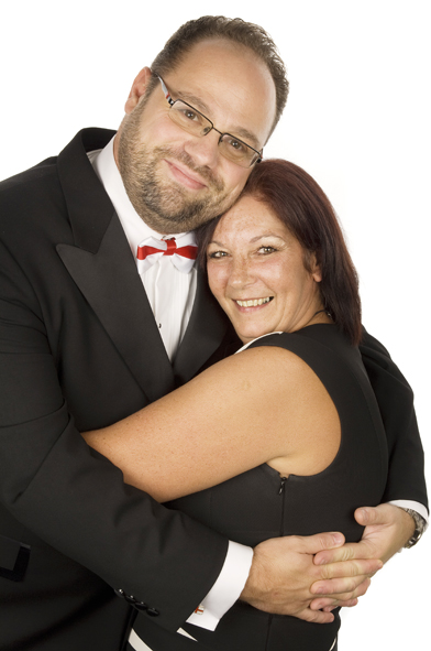 A couple in black tie hugging and posing for the camera. The man has a St. George bow tie