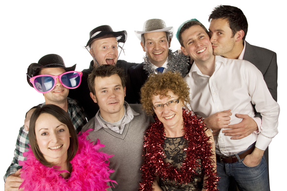 A group posed shot with some wearing our photobooth props and one man hugging and kissing another on the cheek