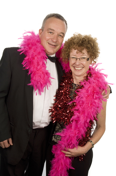 A couple posing in black tie wearing a pink feather boa around both of them