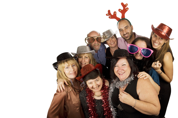 Nine adults posing for a photobooth hire shot, wearing a variety of different photobooth props including antlers, cowboy hats, oversized sunglasses and boas