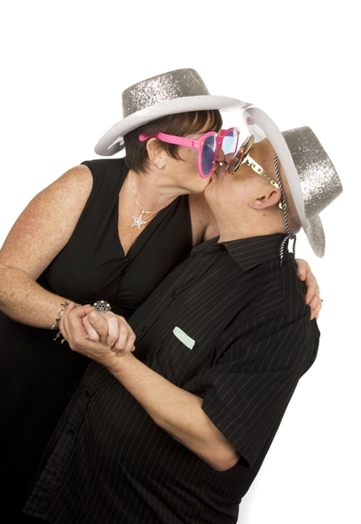 A couple kissing whilst wearing oversized sunglasses and sparkly silver cowboy hats. A shot much easier to obtain when hiring a manned photobooth from Emma-Louise Walton Photography in Burnham