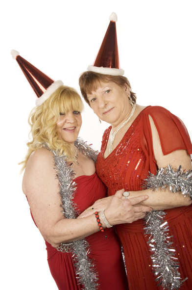 Two ladies posing for a Christmas themed photobooth shot. Both wearing sparkly red party hats with white trim, red dresses, and sparkly silver tinsel