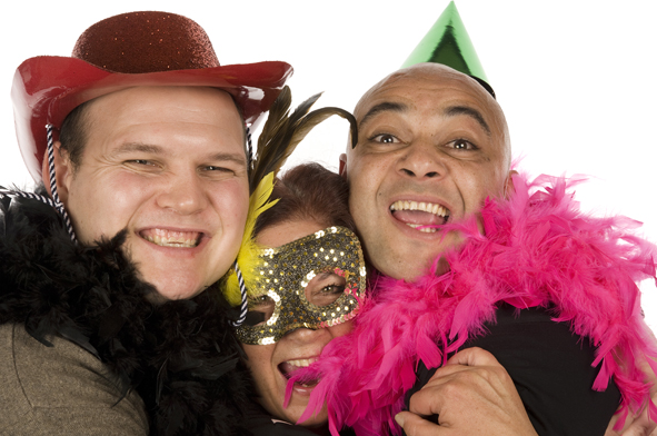 manned photobooth hire image showing three revellers at a party wearing party hats and a feather boa whilst smiling for the camera. Image taken by Emma-Louise Walton Photography in Burnham