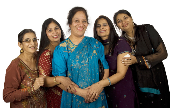 Five ladies wearing sarees posing for a photo and smiling