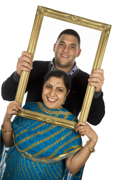 A man and lady posing with a golden photo frame for our photobooth