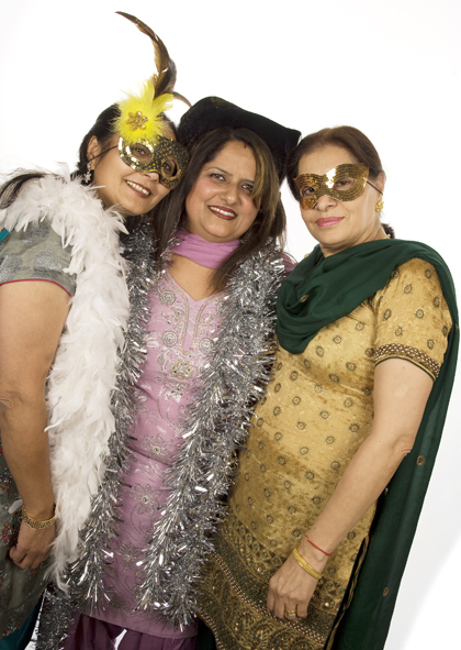 Three ladies posing for our photobooth. Either wearing masks, a cowboy hat, or boas