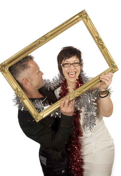 A man and lady posing with tinsel boas, holding a golden picture frame and posing for Emma-Louise Walton as part of her Photobooth hire service based in Burnham