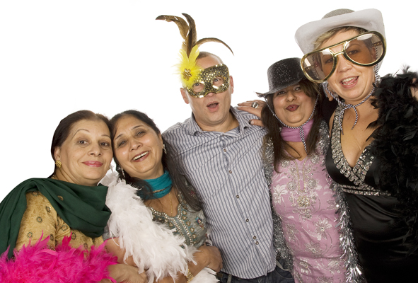 A photo taken using our photobooth hire service in Burnham. 4 ladies and 1 man. The man is wearing a gold mask with yellow and brown feathers. 2 ladies wearing sparkly cowboy hats. The ladies are all wearing feather or tinsel boas