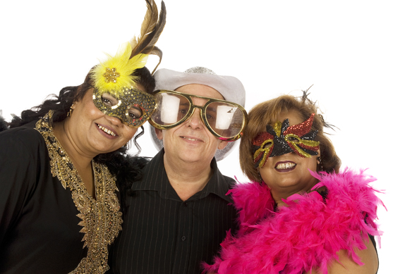 Another of our photobooth hire photos from Emma-Louise Walton Photography in Burnham. Three people posing for a photo. Two ladies both wearing masks, one with a pink feather boa the other with feathers in her hair. A man wearing oversized sunglasses and a silver sparkly cowboy hat