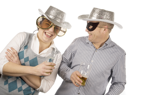 Photobooth shot showing two people holdind drinks and laughing. One wearing over-sized sunglasses, the other a mask and both wearing sparkly siver hats.