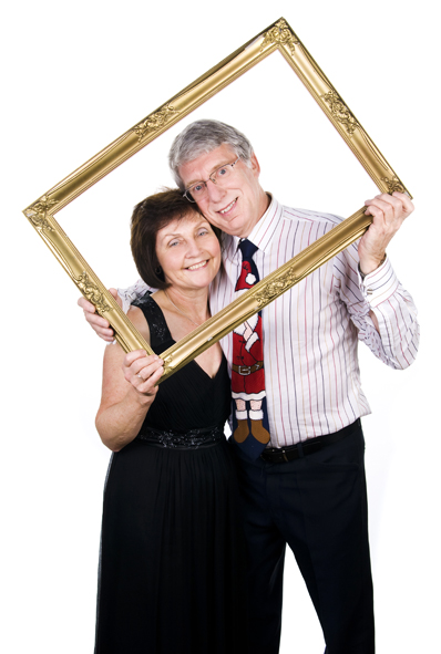 photobooth hire shot showing a smiling couple holding up a golden frame