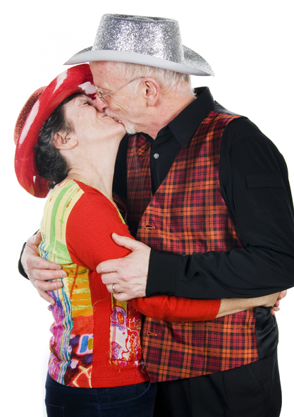 Kissing couple wearing party cowboy hats and brightly coloured clothing