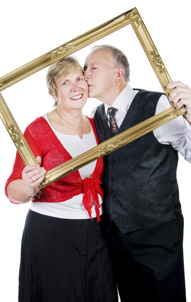 Photobooth hire shot showing a couple holding up a gold frame whilst the man kisses his wife's cheek